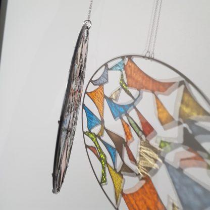 Projection sur une mur de la lumière d'un attrape-rêve en vitrail